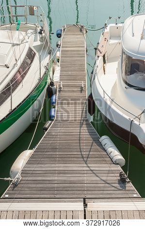 Small Boats Moored To A Jetty In A Calm Water Ocean Marina