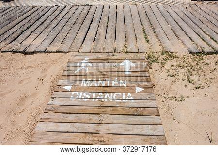 Social Distance Sign On Beach Walkway In Spain
