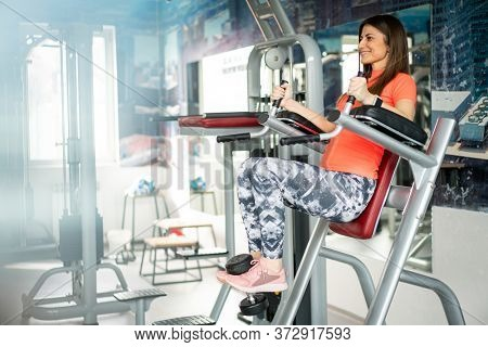 Young fit woman using abdominal machine in gym
