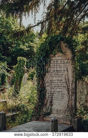 London, Uk - June 16, 2020: Close Up Of A Tombstone With Overgrown Ivy Inside Hampstead Cemetery, A