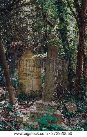 London, Uk - June 16, 2020: Cross Amongst Tombstones Inside Hampstead Cemetery, A Historic Cemetery