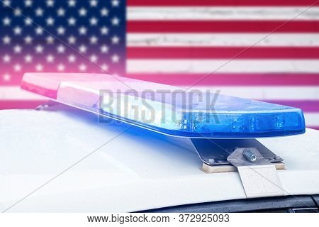 Police Car With Red And Blue Lights On A United States Of America Flag Background