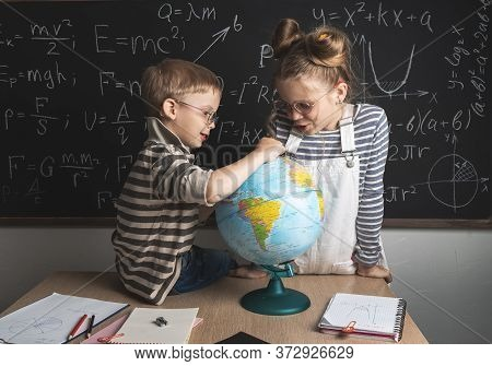 Geography Lesson: A Boy And A Girl Are Sitting On A Desk And Studying The Globe On The Background Of
