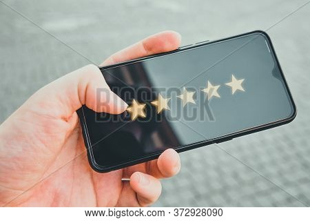 The Concept Of The Highest Rating In The Form Of Five Stars On The Display Of A Smartphone In Hands