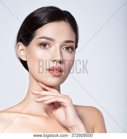 Portrait of beautiful  brunette girl which touching her fresh face. Beautiful face of young woman with healthy fresh skin.  Beautiful face of young adult woman with clean fresh skin. Skin care.