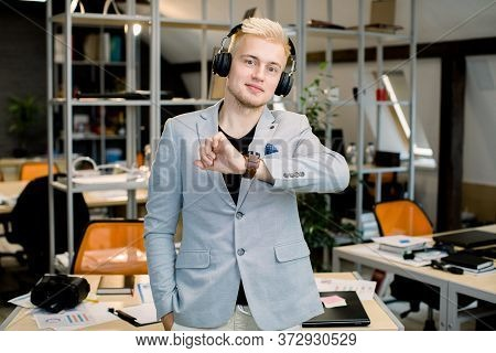 Handsome Confident Caucasian Male Manager Wearing Headphones Looking At His Wrist Watch, Posing To C