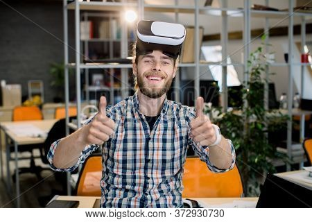 Young Smiling Creative Handsome Bearded Man Working In The Office, Trying A New Product Or Playing G