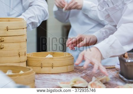 Dim Sum Chefs Working Wrapping Dumplings At Famous Restaurant In Taiwan.
