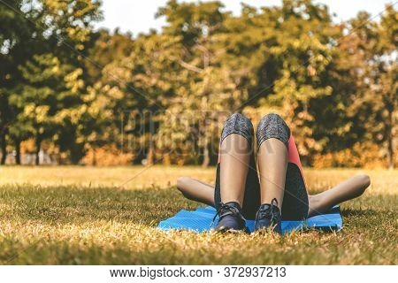 Young Teen Women In Sport Suit Lay Down To Sleep And Relaxing On The Green Grass In The Park After R