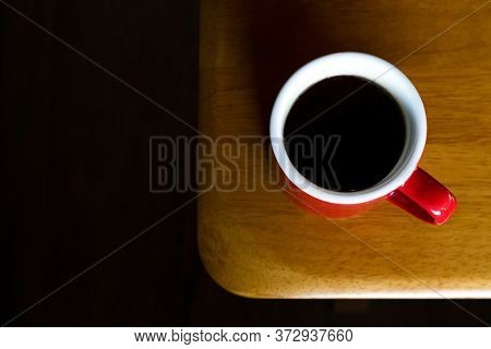 Red Mug Of Hot Americano Black Coffee On The Top Of The Wooden Table With Morning Light At The Coffe