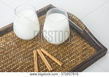 Two Glass Of Vegatarian Rice Milk And Rice Grains Served On A Tray.  An Invigorating Healthy Breakfa