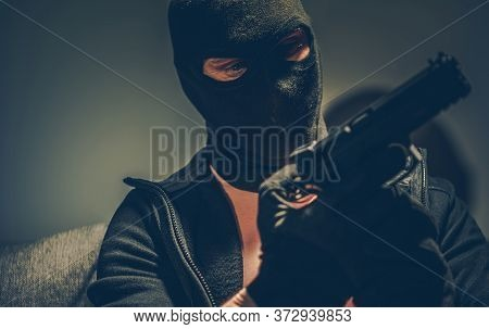 Dangerous Gangster With Hand Gun Wearing Balaclava Mask Preparing For Another Crime. Concept Photo.