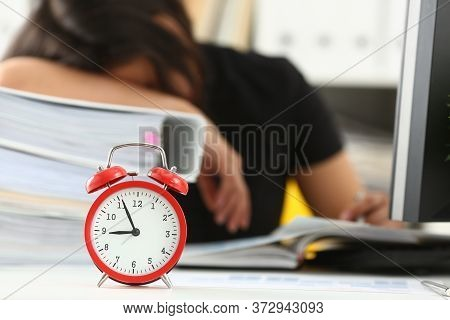 Close Up Of Alarm Clock And Tired Female Worker Taking Nap On Huge Pile Of Document Folders On Blurr