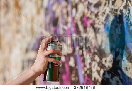 Graffiti Artist Hand Painting With Aerosol Spray On The Wall. Concept Of Colourful Modern Art. Focus