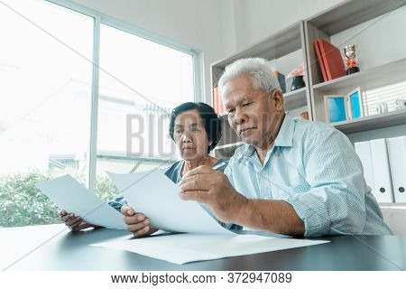 Senior Asian Couple Using The Calculator And Paperwork On Desk At Home To Calculate Expenses And Inc