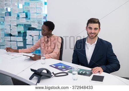 Male and female executives looking at graph in boardroom