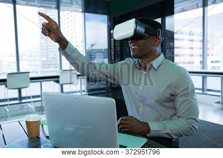 Male executive using virtual reality headset in futuristic office