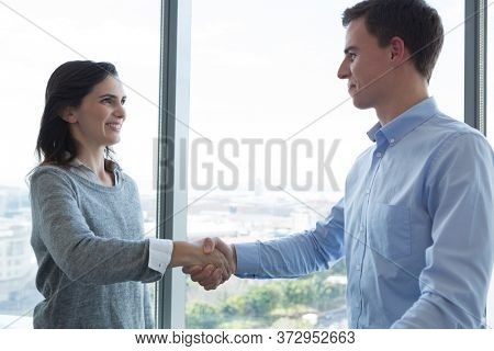 Male executive and female executive shaking hands with each other in futuristic office