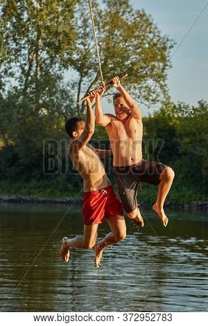 Guys jumping into a river using rope swing