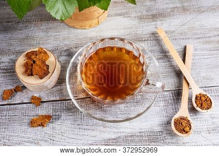 Healing Infusion Of Birch Mushroom Chaga In Figured Glass Cup And Chaga Pieces On Wooden Table. Tren