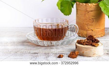 Healing Infusion Of Birch Mushroom Chaga In Glass Figured Cup, Birch Stump With Chaga Pieces On Wood
