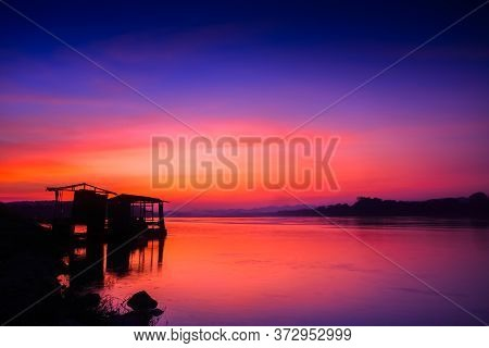 Hut Reflection On Water Under Colorful Sky At Twilight Time Located North East Of Thailand