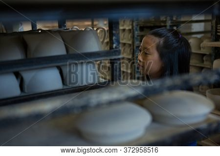 Girl arranging cups in shelf at pottery workshop