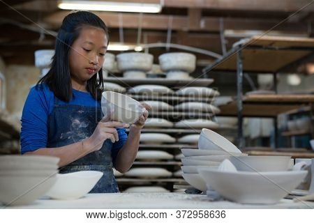Attentive girl checking bowl at worktop in pottery workshop