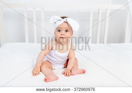 Smiling Baby Girl 8 Months Old Sitting In A Crib In A Children's Room In White Clothes And A Bow And