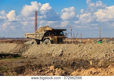 Huge Yellow Mining Dump Truck Working In Iron Ore Quarry. Mining Industry