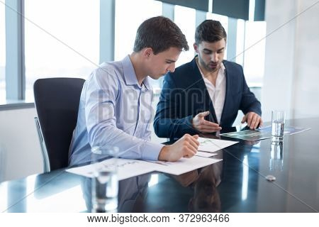 Male executives having discussion over graph in boardroom