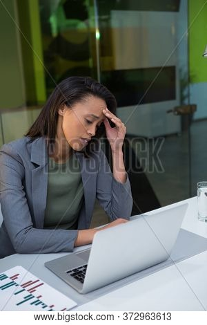 Tensed businesswoman using laptop at desk in office