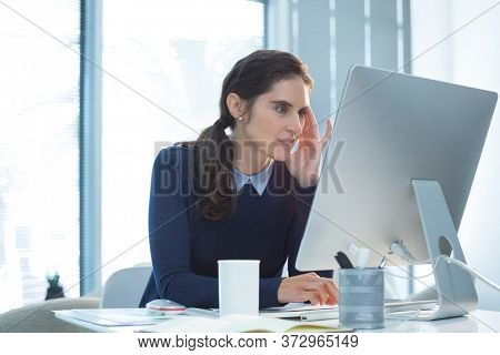 Thoughtful female executive working on computer in office