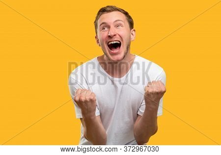 Lucky Man Portrait. Victory Gesture. Amused Guy Celebrating Triumph Shouting Isolated On Yellow Back