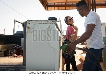 Man filling petrol in car while woman standing at petrol pump station on a sunny day