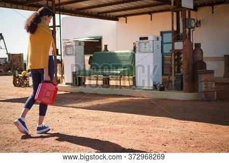 Woman walking with a petrol can at petrol pump on a sunny day