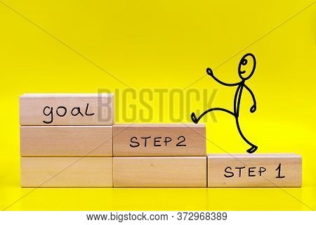 Figure Of A Little Man Running To The Goal By Stacked In The Form Of A Ladder Wooden Blocks On Yello