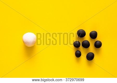 One Big White Ball And Many Black Smaller Plasticine Balls In A Group. Concepts Of Race And Racism.