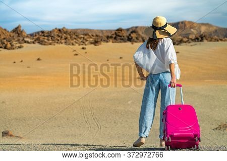 Girl Walks In A White Shirt And Hat With A Pink Suitcase On A Volcanic Sandy Scenery. Teide Volcano,