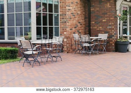 Empty Patio In Summer In Recreation In The Town. White Wooden Table And Armchairs On Outdoor Terrace