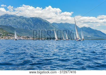 Seven Sailing Boats In The Adriatic Sea On The Background Of The Coast With A Village On A Sunny Sum