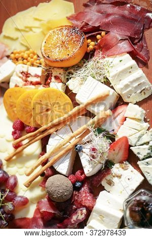 Slicing Up Delicious Delicacies. Pieces Of Different Types Of Cheese, Sliced Sausages, Slices Of Per