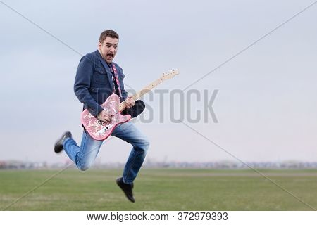 Guitar hipster guy jumping and playing funky rock music outdoors. Happy active male guitarist having fun with his electrical musical instrument outside, over blue sky