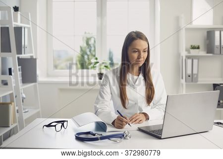 Doctor Woman Listening To A Patient Has A Laptop Web Chat Sitting At A Table In A Clinic Office. Onl
