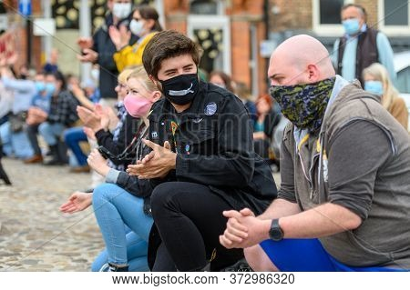 Richmond, North Yorkshire, Uk - June 14, 2020: Protesters Wear Face Coverings While Kneeling And Cla