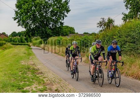 Beek, South Limburg / Netherlands. June 14th, 2020. Small Group Of Cyclists Pedaling On A Rural Road