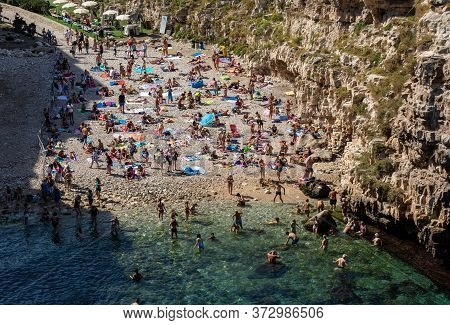 Polignano A Mare, Italy - September 17, 2019: People Relax And Swimming On Lovely Beach Lama Monachi