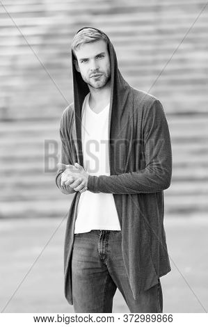Handsome Man With Hood Standing In Urban City Interior. Informal Style Clothing. Fashionable Young M