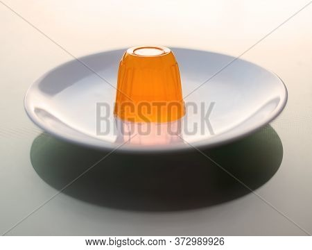 Close Up Of A Orange Gelatin On A White Plate.