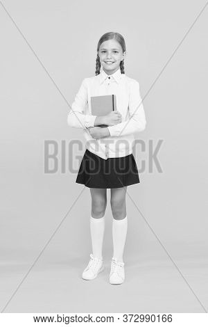 A Firm Knowledge Base For Future. Adorable Small Girl Holding Book On Yellow Background. Cute Little